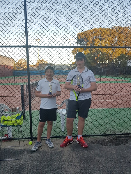 Angus and George holding their tennis trophies